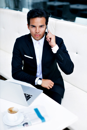 serious face: Handsome confident man dressed in expensive suit with serious face talk on telephone, successful and wealthy businessman sitting front open laptop computer while having cell phone conversation in cafe Stock Photo