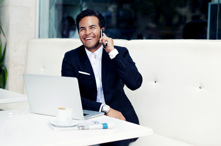 Smiling successful businessman sitting in modern expensive restaurant with open laptop and cup of coffee, wealthy happy man in a luxurious suit talking on smartphone and looking so happy and satisfied