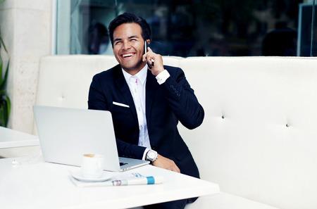 Sourire d'affaires prospère assis dans un restaurant cher moderne avec un ordinateur portable ouvert et tasse de café, riche homme heureux dans un costume de luxe parlant sur smartphone et l'air si heureux et satisfait Banque d'images - 58108739