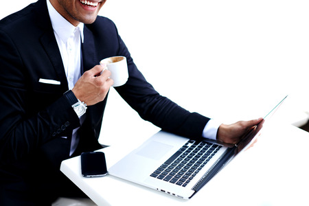 rich life: Cropped image of wealthy smiling man holding the cup of coffee while sitting front open laptop computer, successful businessman looking happy and satisfied during work break in luxurious restaurant