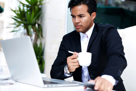 opinionated: Successful male freelancer connecting to wireless via laptop, thoughtful businessman work on net-book while sitting at table in modern coffee shop interior, intelligent man reading news on computer