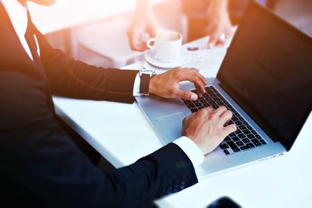 vue de l'image recadrée des mains de l'homme en élégant costume dactylographie sur ordinateur Lapton avec écran copie espace pour votre contenu publicitaire ou un message texte, homme travaillant sur net-book dans un café, flare soleil