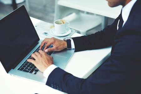 using the computer: vista de la imagen recortada de manos del teclado del hombre en la net-libro con pantalla de copia espacio en blanco para la publicidad o mensaje de texto, hombre rico que trabaja en un ordenador port�til durante la pausa para el caf� en el caf�