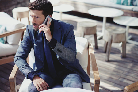 sidewalk talk: Successful businessman talking on smart phone at luxury restaurant terrace, rich man has telephone call, handsome young office worker talk on mobile phone while lunch break in modern cafe outdoors