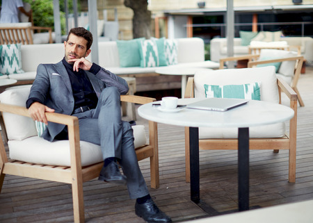 wealthy: Successful intelligent business man relaxing in a luxury restaurant outdoors, confident thoughtful entrepreneur, wealthy men pensive rest and waiting someone in the modern coffee shop terrace Stock Photo