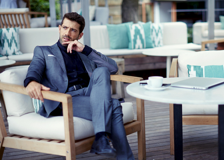 rich life: Portrait of successful businessman in a luxury expensive suit resting at cafe after hard work day and look pensive,rich entrepreneur waiting for a meeting with colleague at open air restaurant terrace Stock Photo