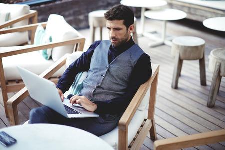 Fiatal sikeres üzletember, dolgozó, laptop ülve kávézó munka közben szünetet ebéd, átgondolt vállalkozó csatlakozik a vezeték nélküli számítógépen keresztül, intelligens férfi szabadúszó munka net-book