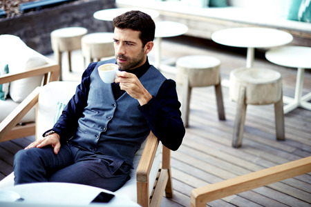 Confident successful businessman in suit enjoying a cup of coffee while having work break lunch in modern restaurant,young intelligent man or entrepreneur relaxing in outdoors cafe looking pensive Stock Photo