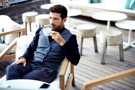 hombre tomando cafe: hombre de negocios seguro y exitoso en traje disfruta de una taza de café mientras almorzaba rotura de trabajo en el moderno restaurante, hombre inteligente joven o empresario relajante en café al aire libre mirando pensativa