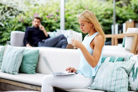 Intelligent femme entrepreneur tenant tasse de café et de travail sur ordinateur, blogueuse utilisant un ordinateur portable pendant sa pause-café, le travail de fille indépendant sur son ordinateur portable alors qu'il était assis au café moderne en plein air