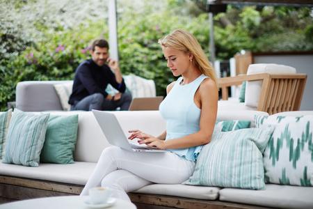 若い女性がカフェで座っている間のラップトップ キーボード テキストを書き込みます成功した実業家作業休憩中に彼女のコンピューター上で動作、