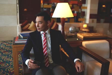 近代的なオフィス、仕事の休憩中に彼の携帯電話の呼び出しを待っている自信を持っているお金持ちの男性起業家に坐っている間携帯電話を保持し