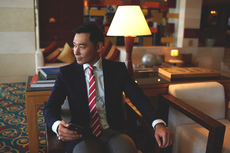 Young successful asian businessman dressed in formal wear holding mobile phone while sitting in modern office,confident rich men entrepreneur waiting for a call on his cell telephone during work break Stock fotó - 58108998