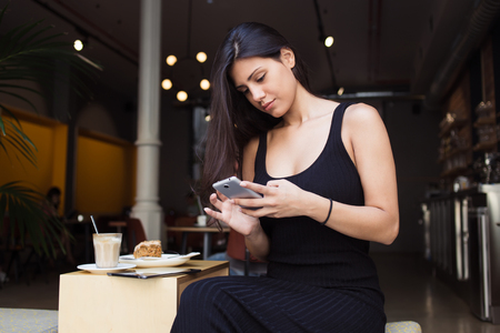 sidewalk talk: Pretty female connecting to wireless on telephone while resting in cozy coffee shop in the fresh air,attractive woman typing message on mobile phone while sitting in cafe terrace during lunch break