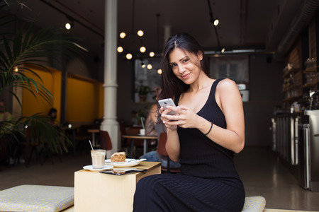 sidewalk talk: Gorgeous female student hold telephone and looking at you while relaxing in sidewalk cafe after lectures, pretty woman chatting on her smart phone while sitting in modern coffee shop outdoors