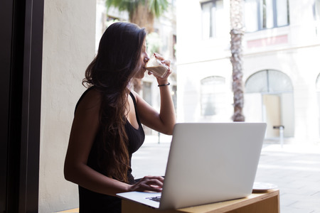 gorgeous woman: Attractive latin female enjoying her drink while working on net-book in cafe outdoors, young business woman using laptop computer for remote work while sitting in restaurant during coffee break