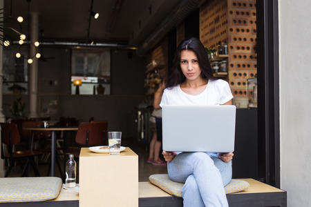 netbook: Young latin woman sitting with open laptop computer in modern coffee shop in the fresh air, female freelancer using net-book for her distance work, student girl learning via portable gadget device Stock Photo