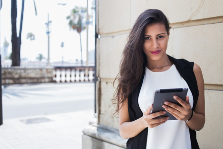 arab model: Half length portrait of an attractive latin business woman holding touch pad while standing on the street in summer day, female student reading news on digital tablet computer after lectures on campus