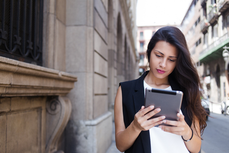 Portrait of a beautiful latin woman reading digital e-book on touch pad while standing on the street in summer day, stylish hipster girl using tablet computer for navigation during walk in the city