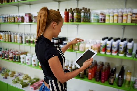 verifying: Young beautiful female consultant checks the quality of cosmetic product verifying information on digital tablet, woman entrepreneur puts pharmaceutical production on trade shelves in her drugstore Stock Photo