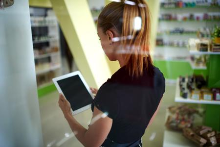 Nő eladó birtok digitális tábla üres képernyő másolatot tér területe a szöveges üzenet vagy tartalom álló kozmetikai üzlet belső, tanácsadó eladó használat touch pad keresni információk Stock fotó