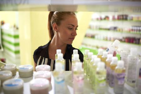 Jonge aantrekkelijke vrouw adviseur legt schoonheid in de winkelrekken, aantrekkelijke vrouwelijke leest de inhoud van het product alvorens een aankoop in cosmetische winkels, koper overwegen aromatische vloeistoffen Stockfoto