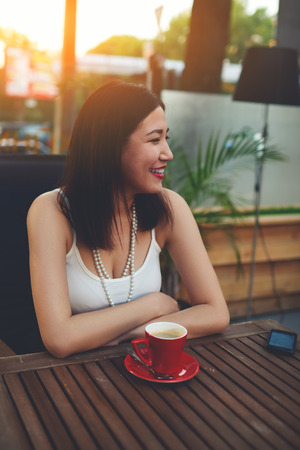 prettiness: Portrait of a happy loveliness asian woman enjoying coffee break recreation time while sitting on in a cozy restaurant outdoors, smiling attractive female have a good time during summer vacation