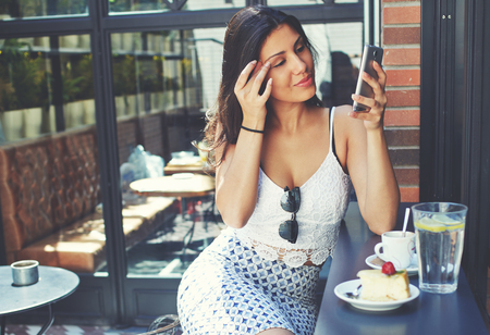 area sexy: Attractive female use her mobile phone as a mirror to touch up makeup in summer day, tourist woman with ideal figure sitting in a cozy coffee shop while breakfast with beverages and delicious desserts