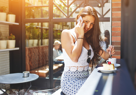 socialising: Young successful businesswoman with gorgeous smile talk on smart phone during her work break in cafe, attractive female laughing at cell phone conversation while breakfast in modern coffee shop, flare Stock Photo