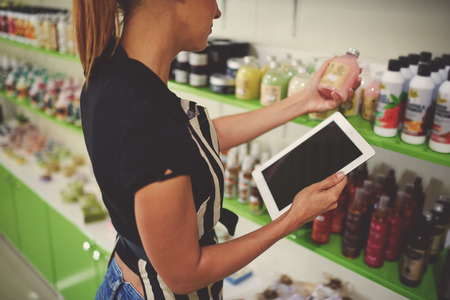 saleslady: Cropped image of saleslady holding cosmetic product in plastic bottle with blank space label while using digital tablet with copy space screen, woman seller reads contents information of the product