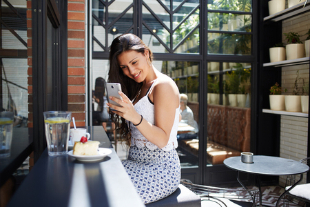 sidewalk talk: Portrait of smiling gorgeous female taking picture of cappuccino cup and berries cake with her smart phone camera, attractive appearance young woman using her cellphone while photographing breakfast Stock Photo