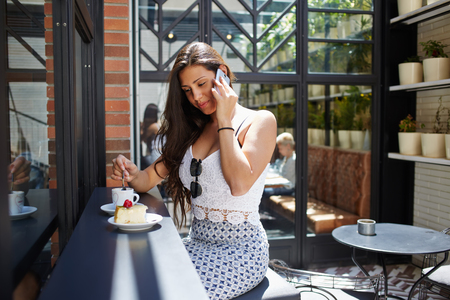 sidewalk talk: Successful businesswoman talk on smart phone while sitting in cafe terrace during with cup of coffee and cake in the sunny day, seductive female model having cell phone conversation while breakfast