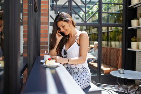 small cake: Smiling female hipster having cell phone conversation while sitting in coffee shop terrace, young successful businesswoman calling via mobile telephone while breakfast with cappuccino and a small cake Stock Photo