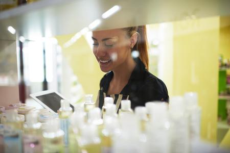 productos de belleza: Mujer sonriente del empresario examina los productos de higiene de belleza en su tienda de cosméticos, consultor de la hembra atractiva del vendedor o cosméticos que estudia mientras que usa la tableta digital para mejorar la calidad del servicio