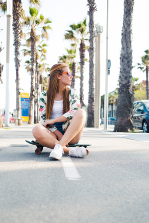 free riding: Trendy woman skater in colorful sunglasses sitting on her skateboard on tropical lane with copy space, young hipster girl dressed in stylish clothing resting after riding during free weekend time Stock Photo