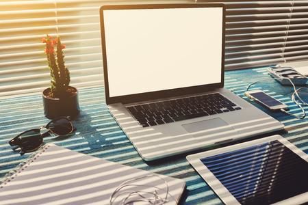 bureau indépendant avec des accessoires et des outils de travail à distance, blanc ordinateur portable écran et tablette numérique, souris, lunettes de soleil, chargeur de téléphone, bloc-notes et plante de cactus, espace de travail d'affaires à la maison ou au bureau Banque d'images