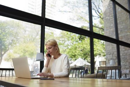 pigiste Femme occupé à travailler dans l'intérieur du loft moderne avec de grandes fenêtres et jardin à l'extérieur, jeune femme d'affaires utilisant un ordinateur portable et smartphone, étudiant caucasien regarder à l'écran net-book Banque d'images