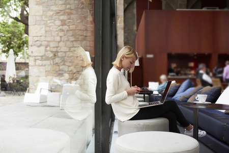busy person: Female freelancer connecting to wireless via smartphone while having a coffee in modern cafe interior, modern business woman working on her net-book sitting at library or loft studio with big windows Stock Photo