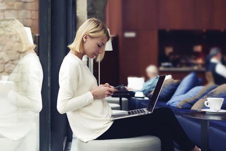 現代のビジネスの女性や若い成功の作業スマート フォンやラップトップ コンピューター技術、インターネットの距離の仕事を使用して図書館で座っ