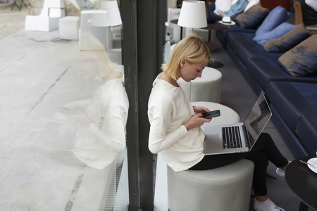 netbook: Female student typing text message on smartphone sitting at library with open laptop computer, freelancer woman working on net-book in modern coffee shop interior, young businesswoman at coffee break Stock Photo
