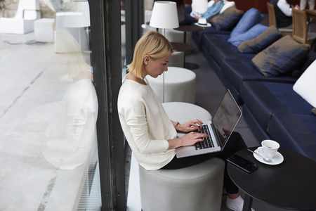 Modern business woman or young successful working on laptop computer while sitting at coffee shop interior, female student sitting in university library with net-book, internet distance work concept Stock Photo