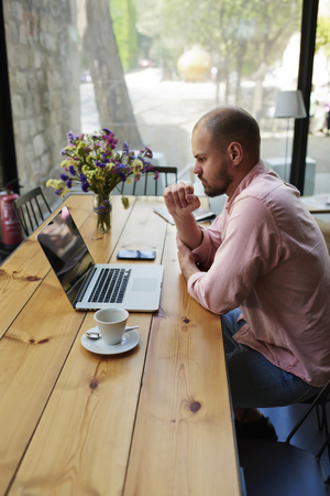 coursework: Male freelancer connecting to wireless via laptop computer, thoughtful businessman work on notebook while sitting at wooden table in modern coffee shop interior, student reading text or book in cafe