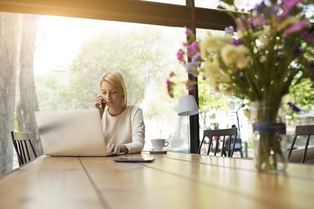 ネット予約画面を見ながらスマート フォンで話すモダンなコーヒー ショップ インテリアは、女性一人でフロント オープン ラップトップ コンピュ