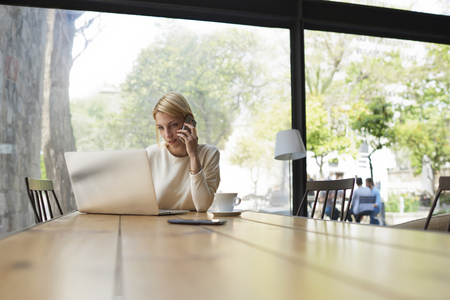 netbook: Gorgeous female speaking on mobile phone with smile while sitting at wooden table with open laptop computer, young student or businesswoman at work break with net-book in modern coffee shop interior