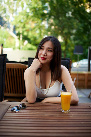prettiness: Portrait of cute asian woman sitting alone at modern coffee shop terrace in the summer day and posing for the camera, stylish female waiting for someone in cozy restaurant outdoors against the park Stock Photo
