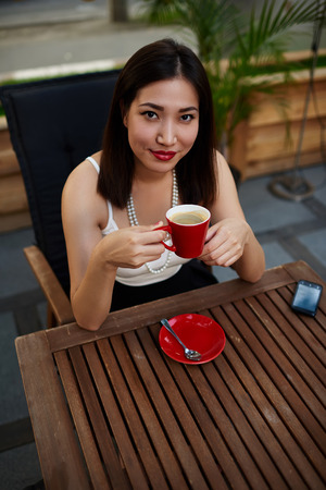 prettiness: Portrait of attractive asian woman enjoying a good day in cozy restaurant outdoors, charming and pretty female hipster holding a cup of coffee sitting on the terrace of sidewalk cafe in summer day Stock Photo