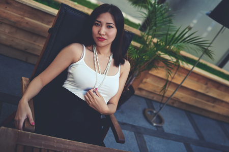 hot asian: Portrait of a lovely young asian woman sitting in a cozy restaurant outdoors and posing to the camera, stylish attractive woman relaxing in a cafe after active city walk, filtered image