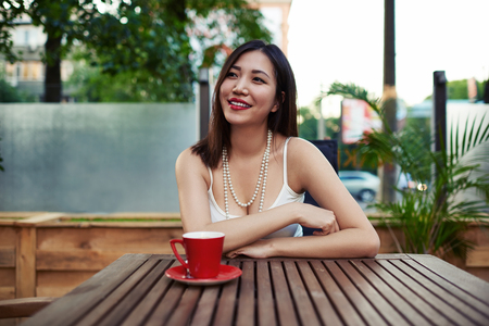 prettiness: Portrait of a beautiful smiling asian woman enjoying a beverage while sitting at wooden table in a cozy sidewalk cafe, happy young and gorgeous  female relaxing after walking in summer day