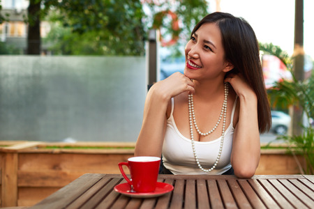 prettiness: Beautiful smiling model posing for the camera while sitting in a modern coffee shop outdoors, happy woman relaxing after work day, wonderful asian looking to the copy space area for your text message Stock Photo