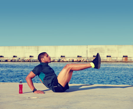 working model: Muscular build man doing hard legs exercise before start his run at sunny afternoon outdoors,afro american sports man working out at copy space area for your text message on advertising content on top